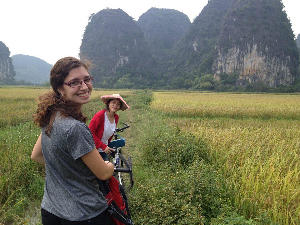 Frederike, accompagnée de Linh traversant un champ de riz